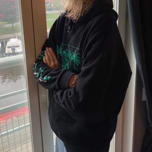 En svart hoodie med grönt tryck och text på ena armen.