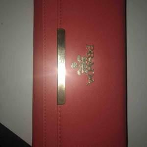 En fejk Prada plånbok med mycket utrymme och plats för både kort och kontanter mm. Aldrig använd. Aprikos/Rosa färg.