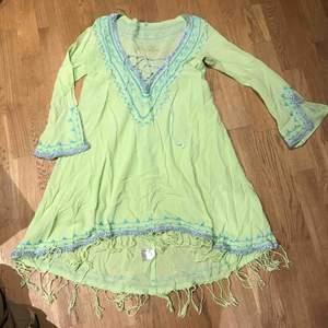 Underbar strandklänning från Fo Lou. Fransar nedtill och längre bak än fram. Limegrön med turkosa broderier.