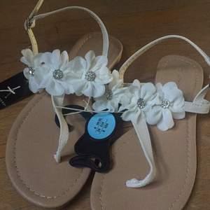 Helt nya sandaler, aldrig använda. Köpte ett par likadana blå också så säljer de vita. Fina med blommor och glitter detaljer.