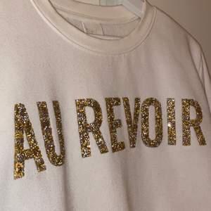 """Vit collagetröja med texten """"Au revoir"""" (hejdå på franska) i guld och silver glitter. Använd max 4 gången, i toppen skick🤎🤗"""