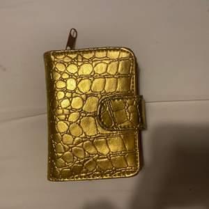 """Säljer denna oanvända guldiga plånbok. Den är i jätte bra skick och har även många """"fickor"""". Undrar man över något så är det bara att kontakta mig."""