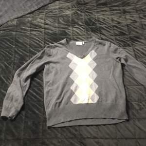 Stickad grå tröja med gula mönster, storlek XL men är liten skulle säga M. Inga deftekter