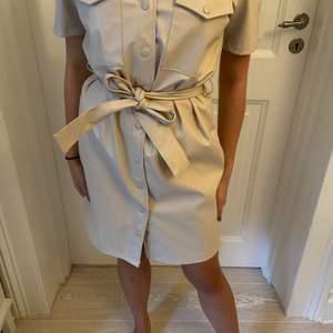 Snygg beige klänning från bikbok i skinnimmitation frpn bikbok. Oanvänd med lapp kvar. Köpt för 800kr i somras.
