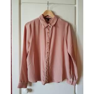 Tunn rosa skjorta med vita detaljer. Lätt transparant.
