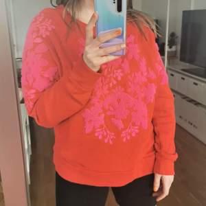 Knallröd sweatshirt med rosa frottébrodyr. Byst 124 cm, längd 63 cm. OBS! Trots att jag tvättat denna tröja flertalet gånger så har det hänt att den torrfält när jag haft svarta byxor på mig. Kan vara bra att veta! Köpare står för porto.