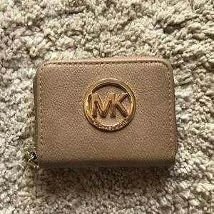 Michael Kors plånbok i beige! Tror att denna är fake, men annars inga defekter så så gott som ny! Finns fickor för kort och en dragkedjeficka i mitten för mynt. GRATIS FRAKT💕