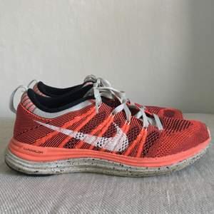 Röd/blå Nike Flyknit One skor med prickig sula, storlek 37, bra skick, använda ett fåtal gånger, 400kr eller högst bud gäller!