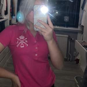 En rosa rhalph lauren polo T-shirt i storlek s, tyvärr är översta knapp sönder men annars väldigt fint skick. Använd under ridning. Frakt beros på vad paketet väger.