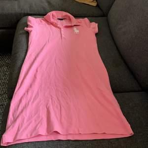 En rosa äkta ralph lauren klänning med krage. Klännngen kan användas med en tjock tröja ovanpå så man skapar en trendig look. Klänningen kommer ej till användning. Passar även om du har S.
