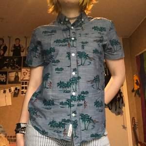 En skjorta med Hawaii mönster. Har en bröstficka och kragen håller ner kragen. Kan mötas upp i Stockholm eller posta. Frakt 44kr. Meddela mig om eventuella frågor:)