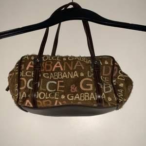 dolce & gabbana väska jag fick av min mamma. ingen aning om den är äkta men jättefin i vilket fall. dragkedjan är lite trög så man måste va försiktig !