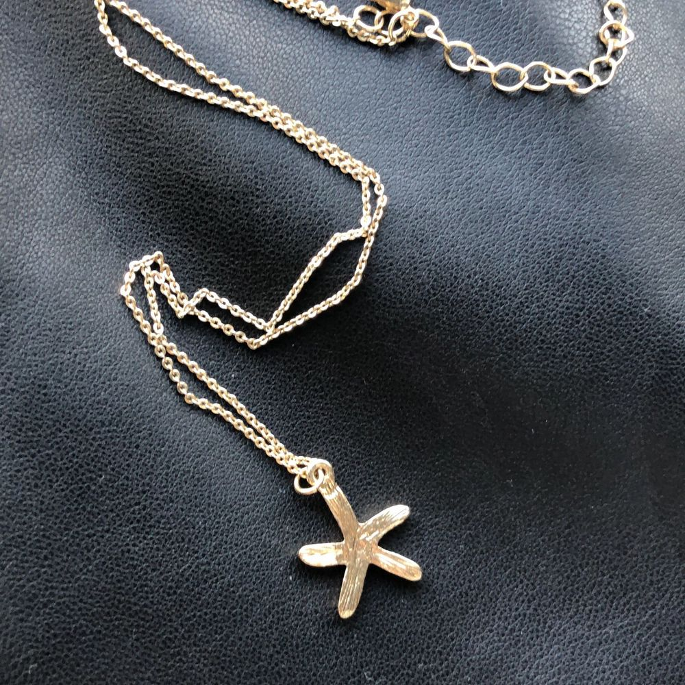 Halsband med sjöstjärna berlock. Har aldrig kommit till använde men otroligt fint. En sida är full av bling och den andra sidan är slät guld plädering. . Accessoarer.