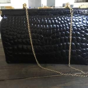 Vintage väska i äkta krokodilskinn.Viss slitage på kanterna på väskan men annars i jätte fint skick. Flärpen syns på bild är trasig men kan lagas.Lås på väskan, nyckel till så man kan låsa.Mått: L30,5 cm H21,5 cm.