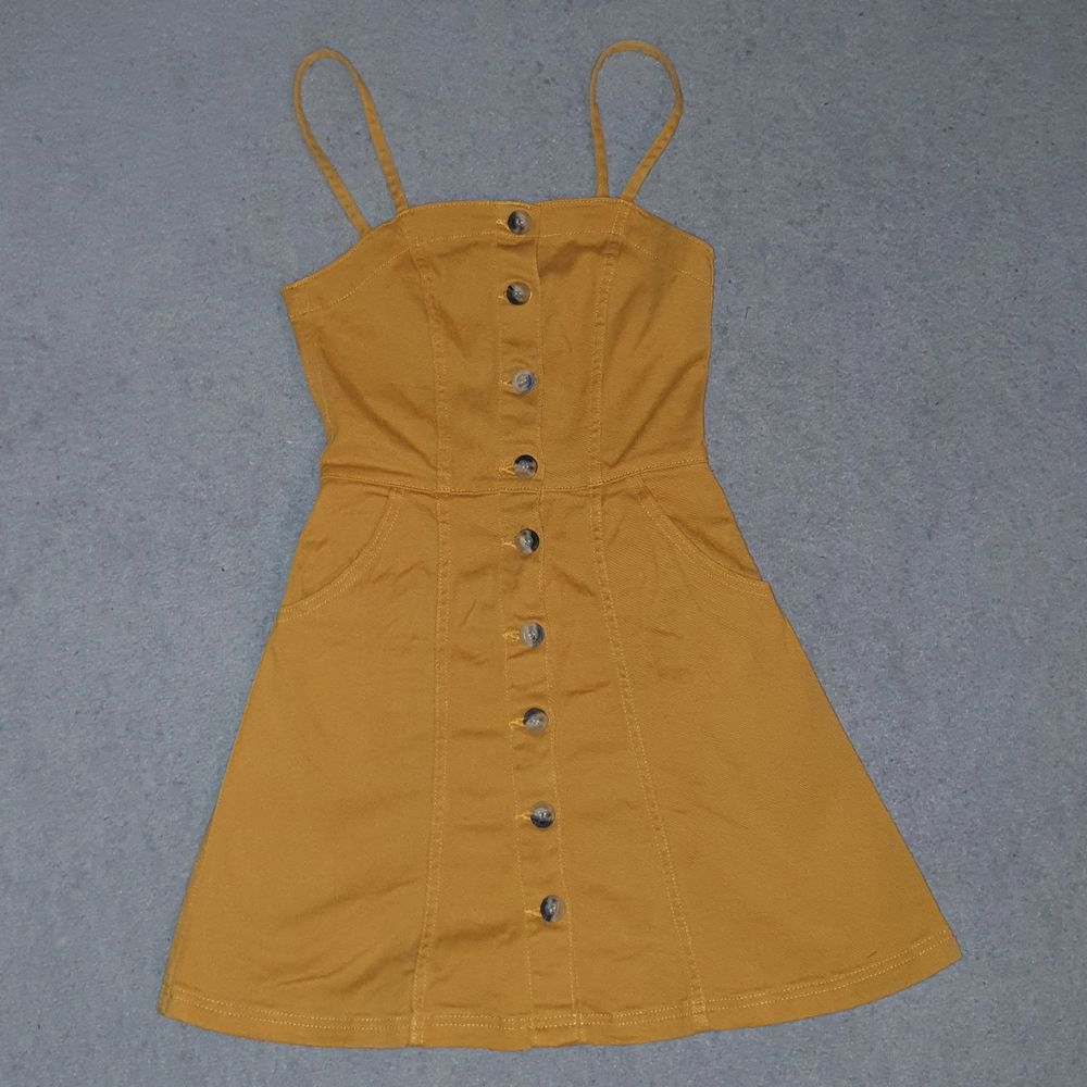 Senapsgul jeansklänning från h&m knäppning i fram med fickor. Ger en jätte fin form på kroppen, aldrig använd. Köparen betalar frakt 66kr :). Klänningar.