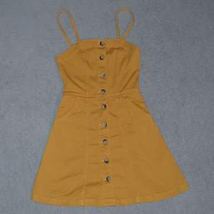 Senapsgul jeansklänning från h&m knäppning i fram med fickor. Ger en jätte fin form på kroppen, aldrig använd. Köparen betalar frakt 66kr :)