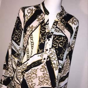 Superfin blus från Gina tricot i svajigt material. Svarta dekorativa knappar längs mitten och i slutet av ärmarna. Blusen är i toppskick! Endast använd ett fåtal gånger.