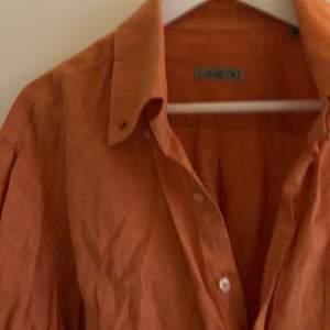 Orange skjorta i linne material. Inga hål eller fläckar men lite skrynklig.