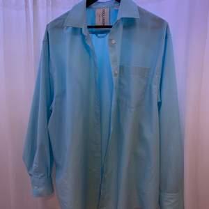 Blå oversized skjorta från asos, collusion. Storlek 38. Aldrig använd. Samma skick som när den köptes. Passar som klänning eller skjorta över ett linne. Frakt ingår inte i priset.
