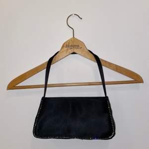 """Liten handväska i fint skick med dragkedja och """"diamantdetaljer"""". Dragkedjan till innerfacket är tyvärr trasig."""