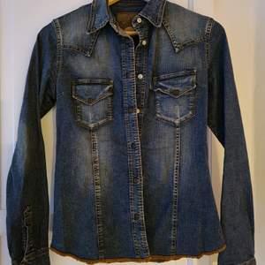 En supersnygg jeansskjorta av kända märket Gul&Blå i den perfekta färgen denimblå. Lite stretchig I materialet och har markerad midja. Kända detaljer på så som sömmen och märket på fickan finns tydliga samt tryckknappar. Strl S. Helt ny. Oanvänd. Inga defekter. Köpt för 799,-  säljer för 399,- Hämtas upp el så står köparen för frakt.