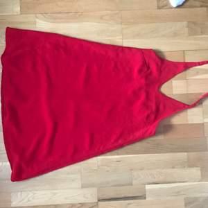 Rymlig röd klänning som man knyter i nacken. Jättefint material och använd en gång.