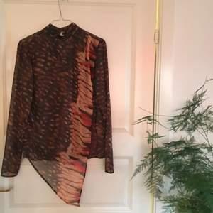 Fin, oanvänd omlottblus i brun/svart mönster. Snygg till långbyxor eller kjol, vardag eller fest. Nypris 899kr. Märke Vintage By Fé.