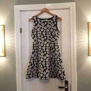 Mörkblå klänning med härligt blom-mönster. Obs är liten i storleken och kort!