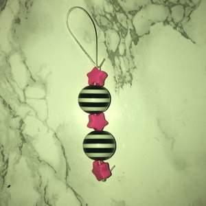 Hemmagjort nyckelring med en stor svart och vit randig färla och rosa stjärnor den är i bra skick och den är jättefin