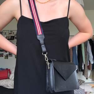 Svart Väska med ett kockare band i färgerna röd,blå och vitt❤️💙 man kan ta av bandet och sätta på ett nytt om så önskas