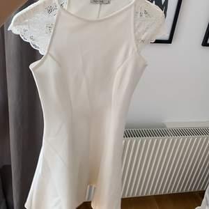 Såå fin vit figursydd klänning från Nelly. Säljes pga för liten. Spets på ärmen och figursydd som gör den väldigt smickrande. Använd fåtal gånger.