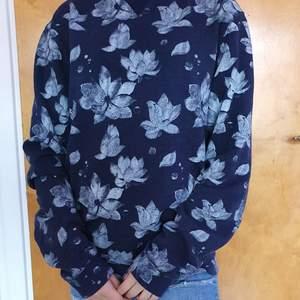 Mörkblå sweatshirt med vitt blommönster! Köpte på second hand men kom aldrig till användning! Köparen står för frakt eller så möts vi upp i göteborg😀