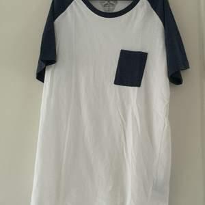 HERR! Vit t-shirt med blå ärmar och ficka. Storlek L. Lager 157. Använd fåtal gånger. 50 kr. Köparen står för frakten! 🌸