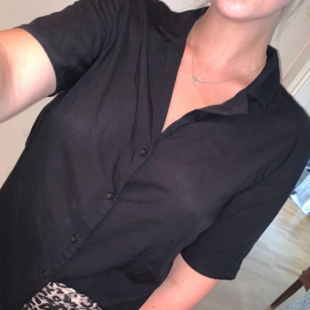 Snygg klassisk t-shirtskjorta i ett tunt härligt material med svarta knappar. Aldig använd pga lite liten i ryggen. Från Gina och bjuder på frakt.. Toppar.
