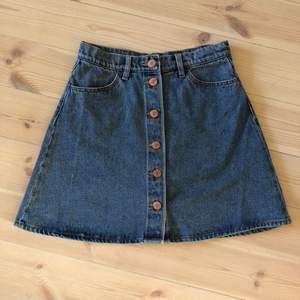 Kort, ljusblå jeanskjol med knäppning fram. Fickor bak och fram. Knappt använd.