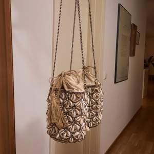 En söt väska från zara, perfekt storlek eftersom den är som en liten säck inuti. Nypris 559:- fint skick alla snäckor och diamanter finns! Pris ex porto