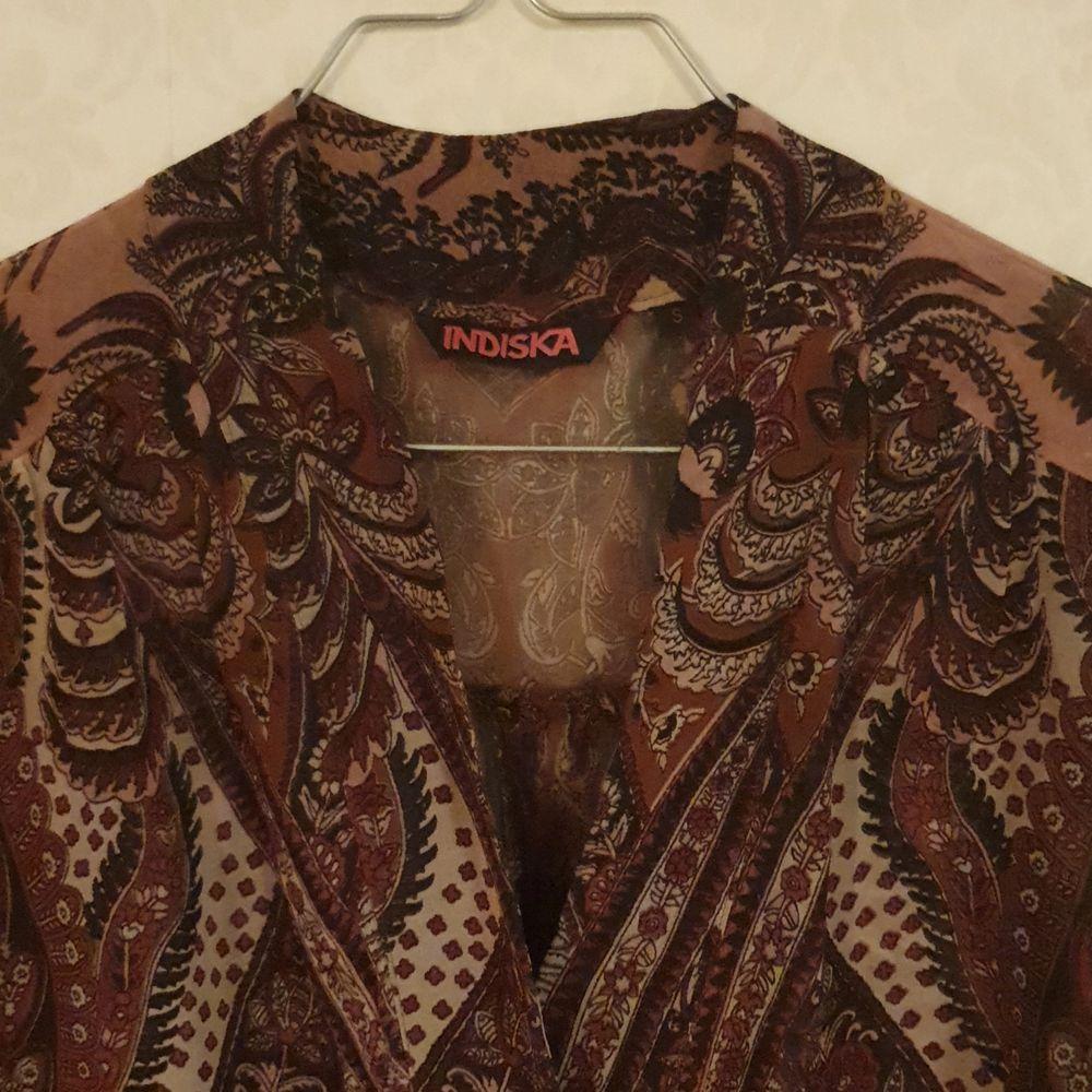 Blus från Indiska, slt.S (sitter som en 36-38:a). med slitsar på sidorna, dold knäppkant, mönstret innehåller fägerna: puderrosa, rostbrun och cerise. På håll uppfattas den som brun-lila tycker jag.. Blusar.