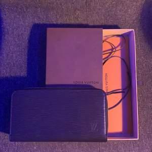 Här är en svart, äkta Lv portmonnä med zebra mönster. Säljer på grund av att den aldrig har använts och bara legat vid sidan av. I boxen får du allt som följdes med när den köptes: protmonnän, en Lv bok, en Lv duk och ett orange paper med Lv märket. Kan tänka mig gå ner i pris vid snabb affär.