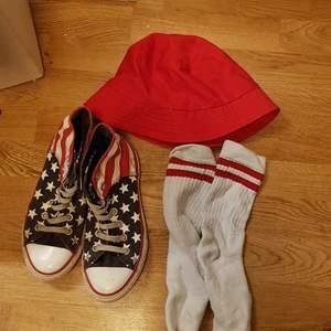 En röd jätte fin bucket hat❤ och ett par riktiga converse med Amerikas flaga på orginal priset på dem var 500 kr. Och ett par strumpor från intersport❤ storleken på buckethaten och strumporna är onesize.