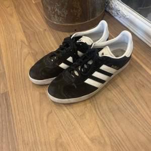 Svarta Adidas Gazell skor med vita ränder. Använda men i fint skick. Köparen står för frakt.