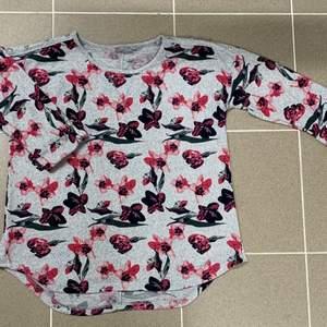 Jätte söt grå tröja med rosa blommor på! Med knappar längst axeln, och uppvikt med knapp i slutet av ärmen. Aldrig använd endast testad!