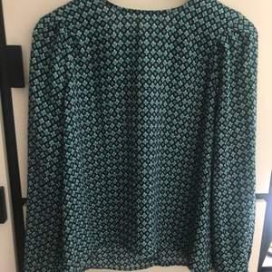 Blus från H&M i fint blågrönt mönster. Storlek 42 (men något liten i storleken). Polyester. Fint skick. 59 kr + frakt