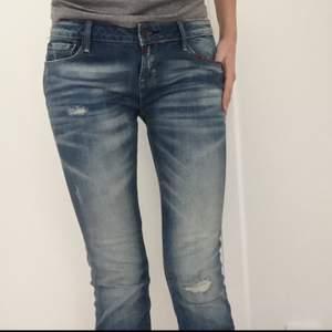 Jeans från Fishbone, slitna och blekta. Har röda detaljer vid fickor (se bild 3).