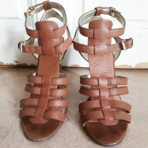 Ljusbruna gladiatorsandaler i läder och kilklack i trä. US size 8 vilket motsvarar storlek 38-39. Sparsamt använda och i fint skick!