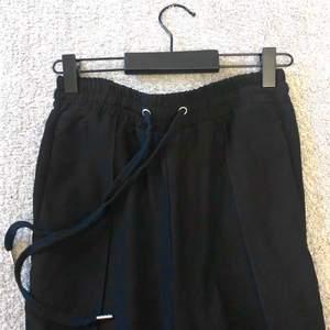 Vida bekväma plisserade byxor. Färg: svart. Dragkedja vid benslut.
