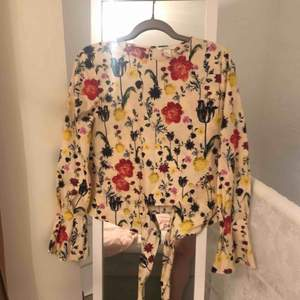 """Oanvänd bomullsblus från H&M med knytdetalj i midjan för mer snäv form, långa ärmar med vekatt """"trumpet""""avslut, fint blommönster 🌼"""