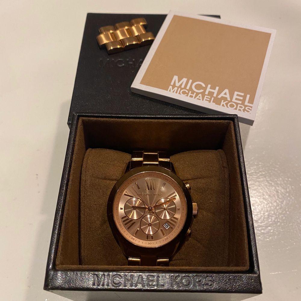 Michael Kors klocka i modell MK5799. Fint skick, men en ytterst liten flisa av på sidan av glaset. Helt nytt batteri! Justerad länk, men avtagen bit ingår vilket gör det möjligt att justera den till önskad längd. Frakt tillkommer. . Accessoarer.