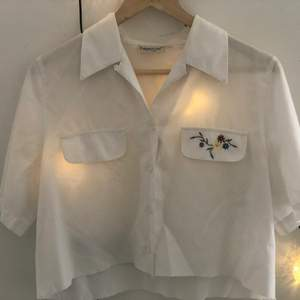 Cropped white button up T shirt with minimal flower embroidery. Easy to shorten to fit more cropped since I am 175cm! U might wanna cut it shorter urself:) *frakt= 63kr