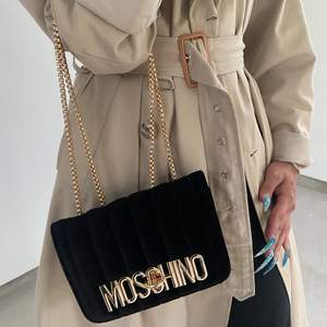 En Moschino handväska i velour-tyg med guldkedja som går att justera efter hur man vill bära upp väskan. Väskan är stabil och har en röd insida av fuskläder och en inreficka. Fraktar för extra kostnad 🦋 (OBS, ej äkta)