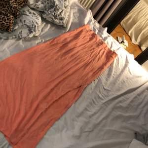 En aprikosfärgad långkjol med en slitt längst benet från vila i stl xs